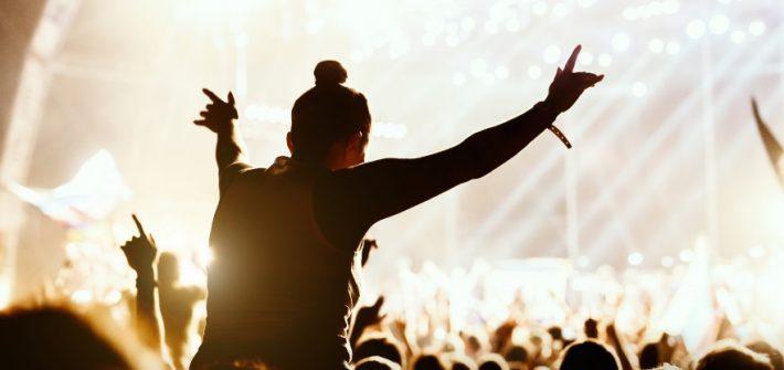 Une femme dans un festival de musique sur les épaules d'une autre personne